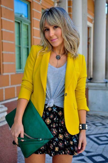 Mulher com saia curta estampada e blazer mostarda.
