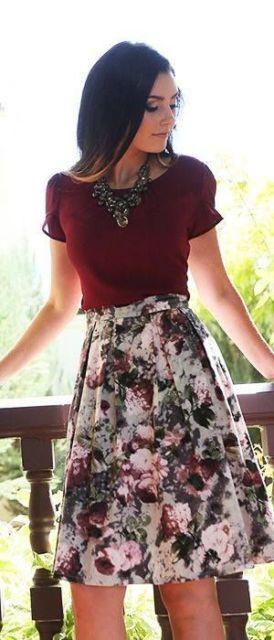 Mulher com blusa bordo e saia curta florida.