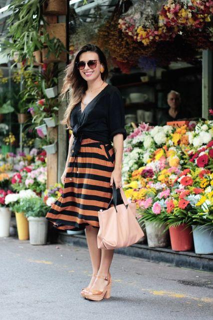 Mulher com saia com listras horizontais e blusa preta.