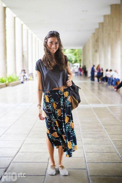 Mulher com saia estampada e camiseta grafite.