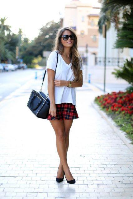 Mulher com saia xadrez e t-shirt branca.