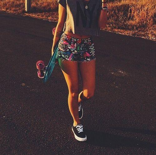 Menina com shorts florido, skate e tênis preto.