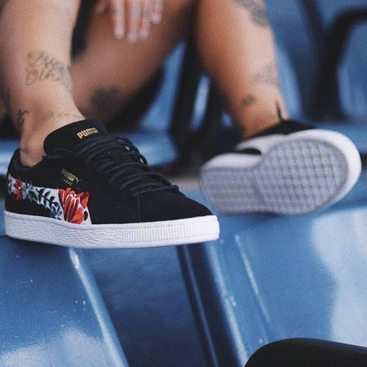 Mulher com pernas tatuadas e tênis preto com estampa.