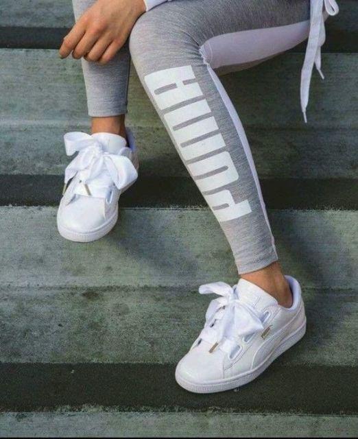 Mulher com legging da Puma e tênis branco.
