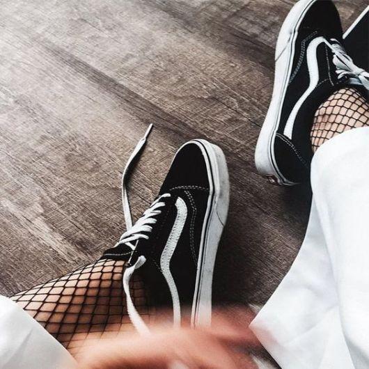 Mulher com tênis preto, calça e meia arrastão.