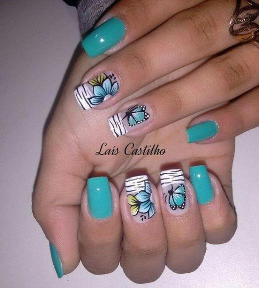 Unhas decoradas com borboletas azuis.