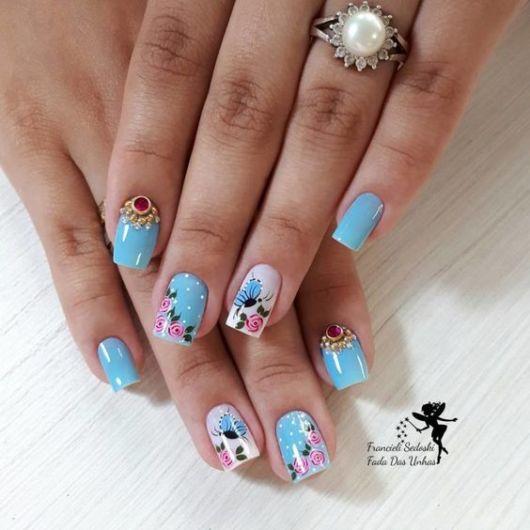 Unhas azuis com borboletas.