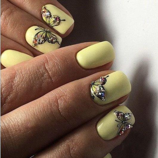 Unhas amarelas com enfeites de borboletas.