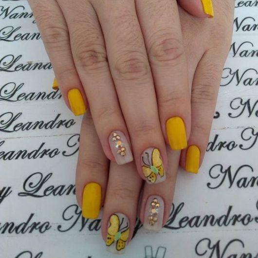 Unhas amarelas com borboletas.