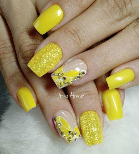 Unhas amarelas com borboleta.