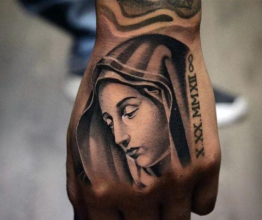tatuagem na mão masculina religiosa