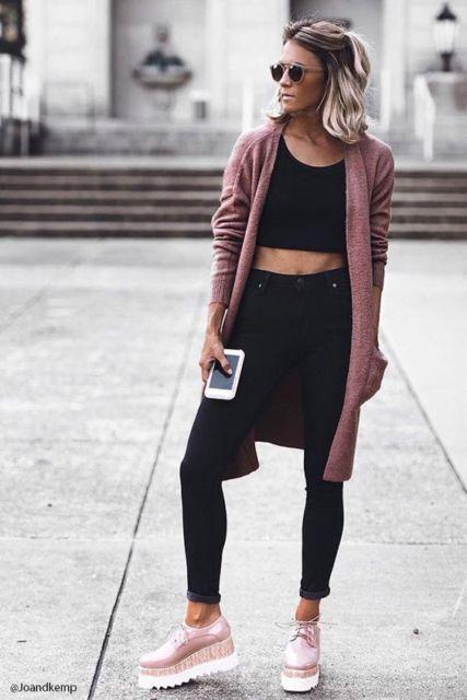 modelo usa blusa preta, casaquinho rosê, calça preta e oxford na mesma cor do casaco.