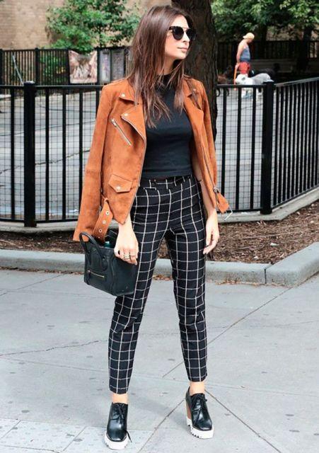 modelo usa calça preta e branca, blusa, casaco suede e sapato.