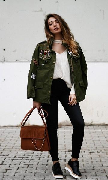 modelo veste calça preta, blusa branca, jaqueta militar, bolsa suede e sapato oxford com salto.