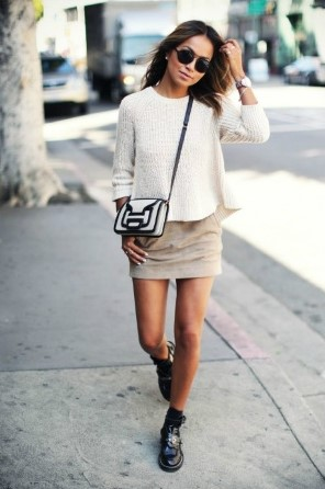 modelo veste saia bege, blusa branca, sapato preto e meia na mesma cor.