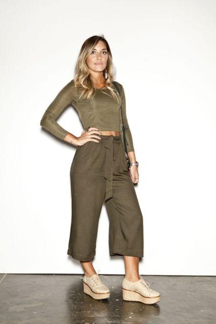 modelo veste calça pantacourt, blusa verde e sapato de salto bege.