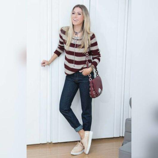 modelo veste calça jeans, sapato bege e blusa com listras horizontais.