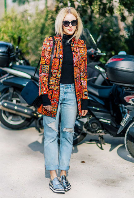modelo usa casaco marrom, blusa preta e jeans.