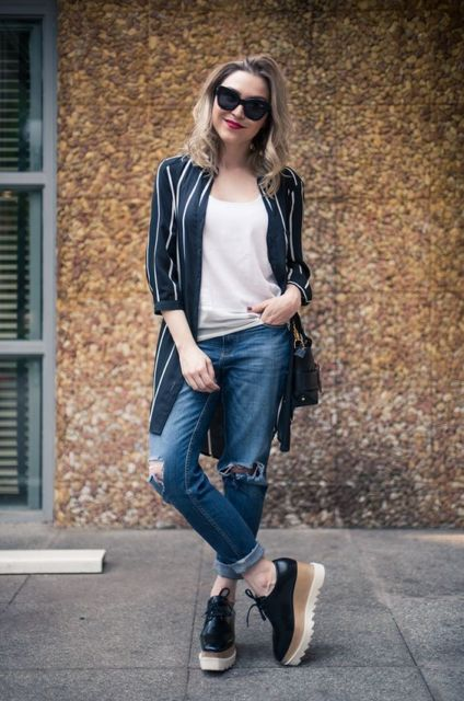 modelo usa casaco longo listrado, calça boyfriend, oxford plataforma e bolsa preta.