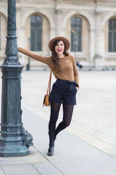 modelo usa short, blusa bege, chapéu e bolsa na mesma cor.