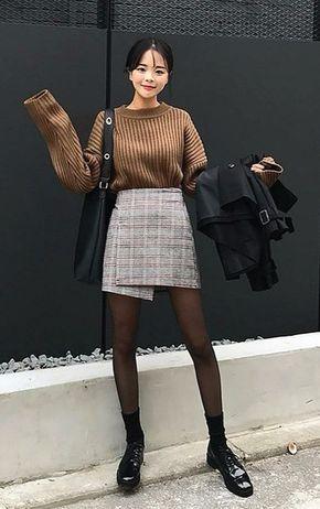modelo usa saia, blusa de lã bege, meia-calça e bolsa preta.