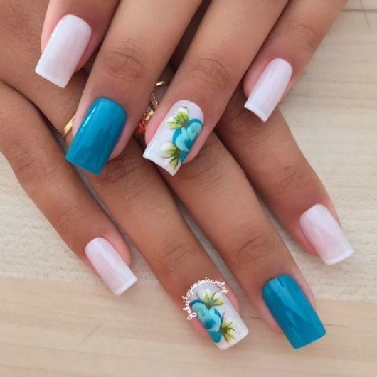 unhas brancas e azul decoradas com flor.