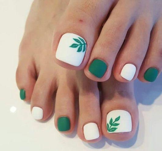 unhas pintadas nas cores verde e branco com desenho de folha.