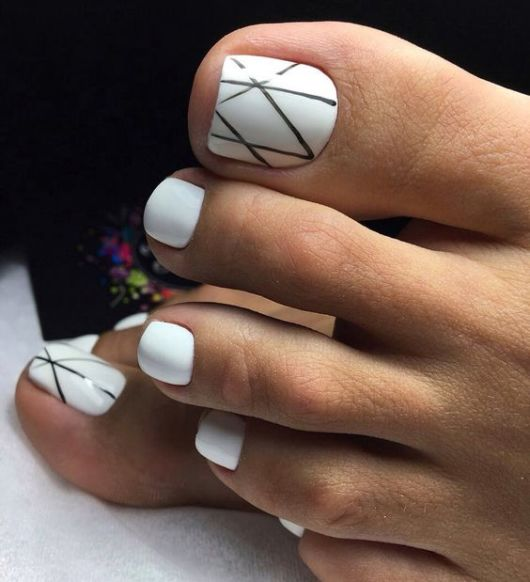 unhas brancas pintadas de branco com decorado de riscos na cor preta.