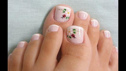 imagem mostra unhas dos pés com decoração de mini florzinhas.