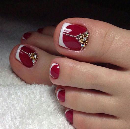 imagem mostra unhas dos pés pintadas de vermelho com francesinha irregular branca e pedrarias.