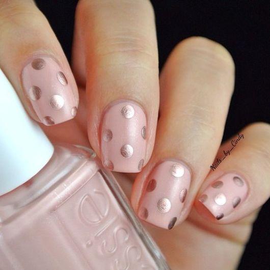 unhas cor de rosa decoradas com bolinhas poá prateadas.
