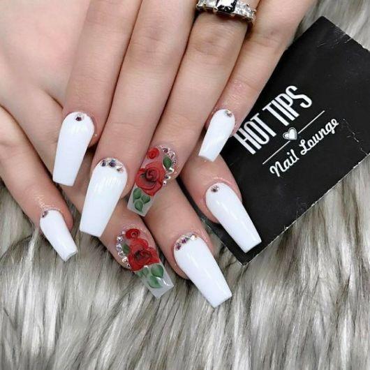 unhas brancas decoradas com flores rosas vermelhas.