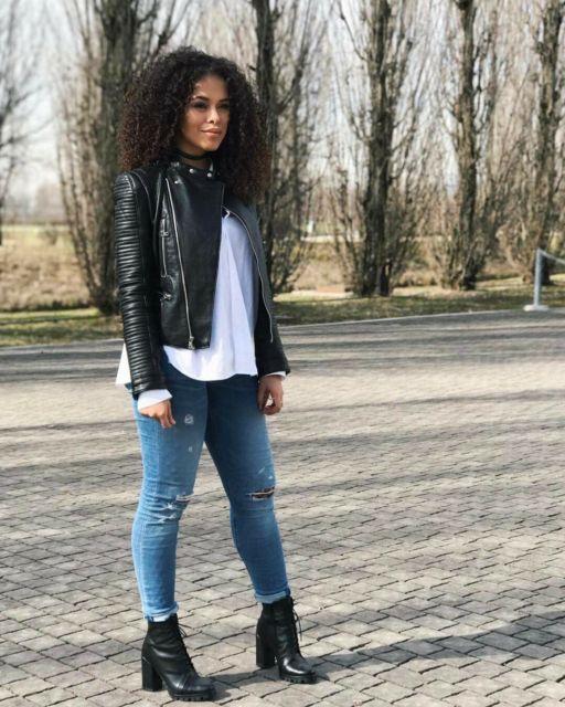 modelo usa calça jeans azul, bota preta, camiseta branca e jaqueta de couro preta.