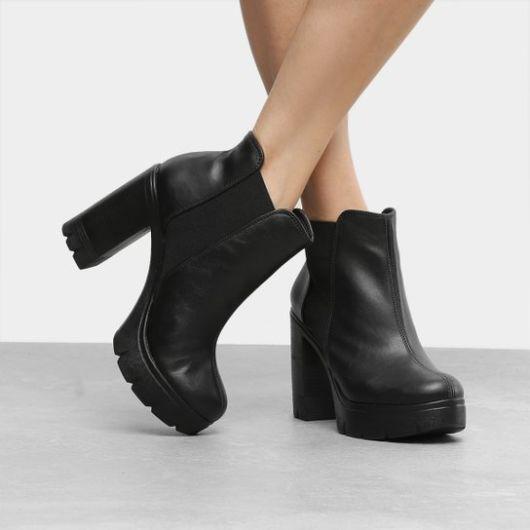 modelo usa bota preta de cano curto.