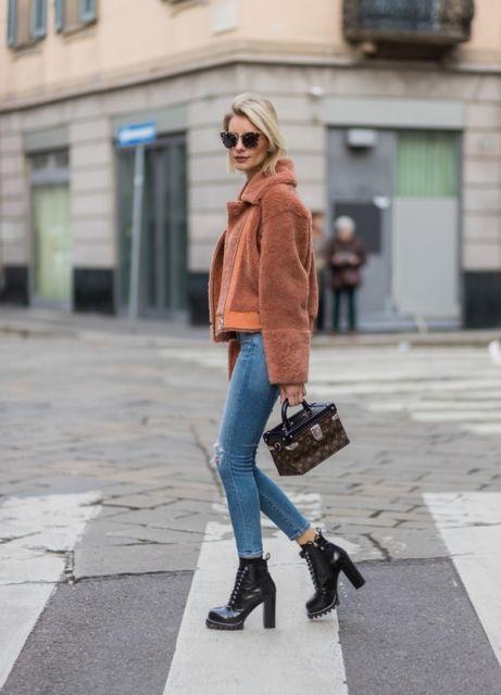 modelo usa calça jeans azul clara, bota de salto alto preta, casaco bege e óculos escuros.