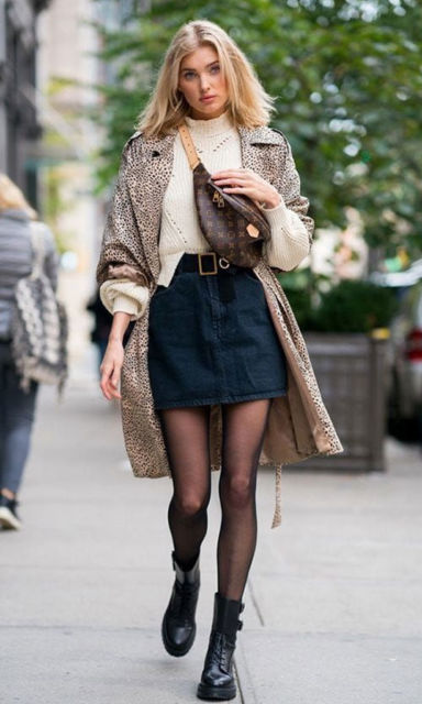 Mulher veste saia jeans escura, meia transparente, casaco longo e bota preta.
