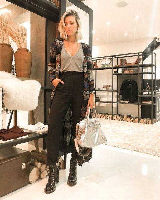 modelo usa calça preta, blusa cinza, maxi cardigã colorido e coturno preto.
