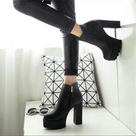 modelo veste coturno preto de salto alto e calça preta justa.