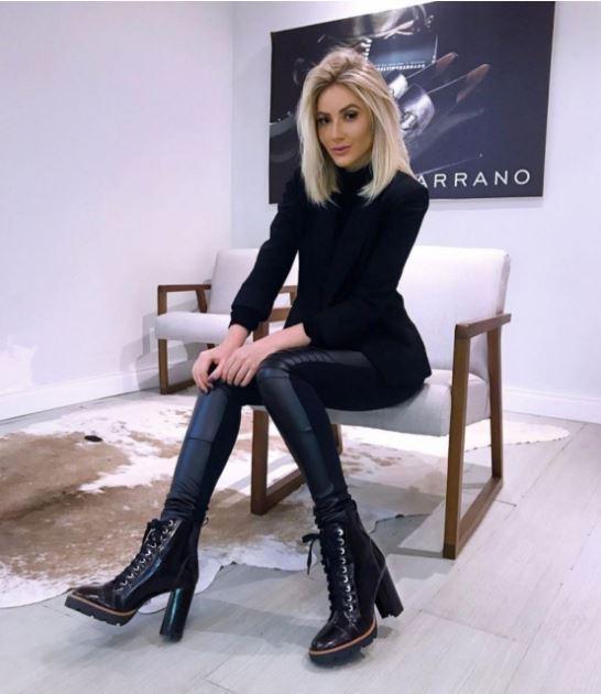 modelo veste blusa preta gola alta, calça de couro preta e bota na mesma cor.