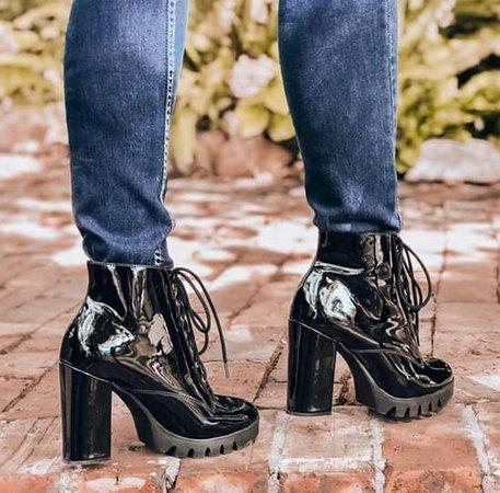 modelo usa calça jeans e bota preta verniz.