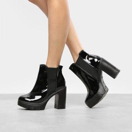 modelo usa bota verniz preta com elástico lateral.