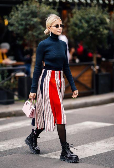 modelo usa sia estampada, meia preta, blusa de gola, bolsa rosa e coturno preto.