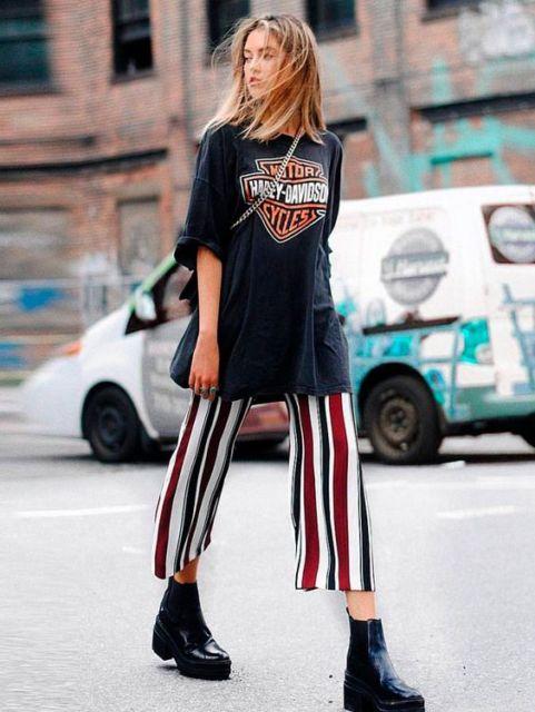 modelo usa calça pantacourt listrada, camiseta preta e bota na mesma cor.