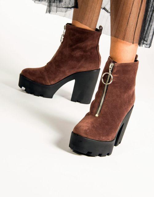 modelo usa bota marrom tratorada de camurça com zíper.