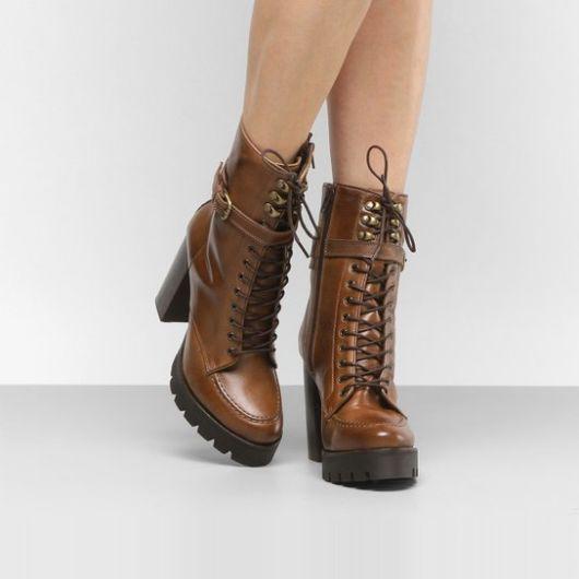 modelo usa bota marrom com cadarço.