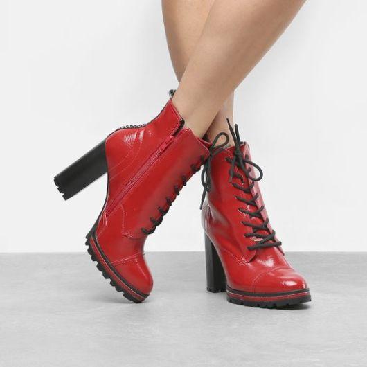 modelo usa bota tratorada vermelha com preto.
