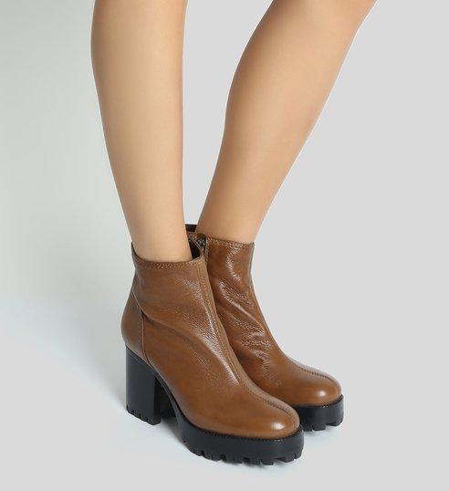 modelo usa bota de couro marrom tratorada.