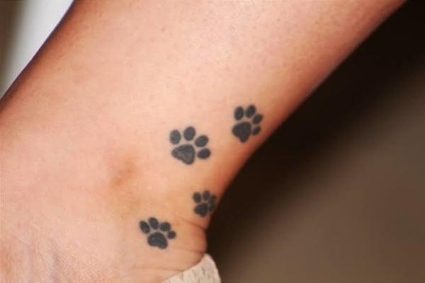 ideia de tatuagem de pata de cachorro na perna