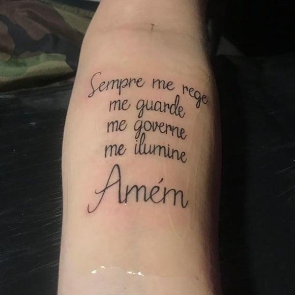 tatuagem de frases no braço masculina com inspiração religiosa