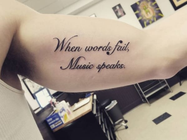 tatuagem de frases no braço masculina de música